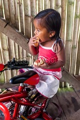Indigenous Girl Eating A Piece Of Bread With Jam (kalypsoworldphotography) Tags: park wild portrait house southamerica girl face bicycle bread person kid ecuador amazon stair pretty child sad looking little expression small poor young reserve dirty bamboo lodge clothes eat hunger national jungle friendly teenager misery tribe shelter jam staring unhappy indigenous cuyabeno amazonia quechua siona yasuni
