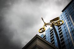 Golden Bicycle (pillarsoflight) Tags: blue windows cloud brown beauty bike bicycle statue oregon 35mm portland prime gold grey aperture nikon adobe pdx 18 pnw vignette lightroom d3300