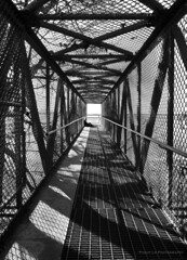 Barophobic (Philip Lo Photography) Tags: bridge blackandwhite bw geometric monochrome contrast lumix alone sitting shadows footbridge britishcolumbia overpass tunnel panasonic chainlink whiterock 43 lx100 microfourthirds dmclx100
