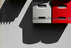 Il dilemma del postino. The mailman conundrum (sandroraffini) Tags: light red urban abstract lines contrast grey shadows details curves surreal mailboxes bologna reality doubt conundrum dilemma fragments