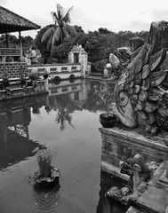Balinese water garden (SM Tham) Tags: bridge trees blackandwhite bali plants building water monochrome reflections indonesia outdoors island pond asia royal statues palace pots pavilion waterfeature stonecarvings pedestal waterjet karangasem amlapura puriagungkarangasem