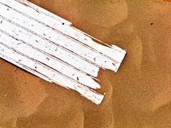 board sinking in sand (friendlydrag0n) Tags: orange white yellow gold amber sand board minimal diagonal sinking