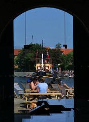 Arch framed. (forkcandles) Tags: blue red england people building yellow architecture bristol boats ship entrance exhibition tables archway tugs johnking floatingharbour cityandcountyofbristol fz1000 forkcandles fz1000panasoniccamera