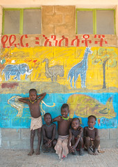 Hamer tribe children in a school in front of a painted wall with wild animals, Omo valley, Turmi, Ethiopia (Eric Lafforgue) Tags: poverty africa school girls people elephant color boys childhood animal vertical painting outdoors photography education mural day african poor tribal ostrich learning bead omovalley giraffe schools ethiopia tribe groupofpeople development hamar developingcountry hamer hornofafrica ethiopian riftvalley wallpaintings eastafrica abyssinia realpeople beadednecklace lookingatcamera ruralscene fulllenght childrenonly turmi indigenousculture blackethnicity ethio161861