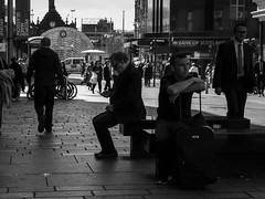 Traveller's Rest (Leanne Boulton) Tags: life street city uk travel light shadow people urban blackandwhite bw white man black detail men travelling texture face mobile composition canon bench four mono scotland living blackwhite eyecontact sitting phone darkness faces natural humanity outdoor expression glasgow candid culture streetphotography streetlife scene human shade 7d posture society depth tone facial candidstreetphotography