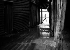 Just passing  (halifaxlight) Tags: bw wet norway walking alley floor pedestrian walls bergen passage bryggen woodbuilding