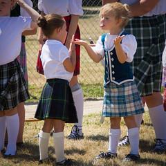 Raspberry (lacygentlywaftingcurtains) Tags: highlanddancers kilt children kids girls cute socks raspberry funny silly childish teasing