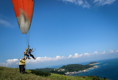Gentle push (photomaster.shifu) Tags: outings adventure paragliding photographer d300 kitlens photography starbursts sunrays sun jump mountain sea sky group blueskies 18140 taiwan taipei wanli specialshots specialmoments flying flyinghigh wind clouds ocean