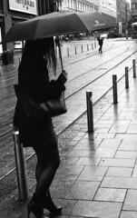 Umbrella series (Emptiness of Helsinki) Tags: blackandwhite film girl rain contrast umbrella finland helsinki europe shadows streetphotography blacks hp5 ilford highiso pushprocess selfdeveloped rainyweather ei3200 yunglady