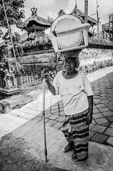 Balancing Act (Many Shades of Grey) Tags: street old blackandwhite bali woman white black lady walking indonesia women basket expression age stick balance plates aged frown heavy wrinkles balancing sarong bersakih