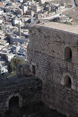 al-Husn Town Crac des Chevaliers Crusader Castle Syria Nov 2010 (eriagn) Tags: travel history architecture photography town war destruction stonework towers middleeast documentary historic unescoworldheritagesite civilwar knights ramparts syria conflict protection fortress garrison homs historicalsite kurds crusadercastle kracdeschevaliers wantondestruction stonetowers hospitaller ancientarchitecture cracdeschevaliers حصن erring medievalcastle alhusn raymondii hisnalakrad concentriccastle castleofthekurds mamluksultanbaibars ngairelawson ngairehart حصنالفرسان‎ knightsofthecrusade الفرسان‎