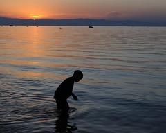 Evening Bath (DJ Cockburn) Tags: africa sunset sun silhouette child greatlakes malawi ripples bathing washing nyasa lakemalawi capemcclear niassa