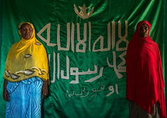 Sufi women worshippers in front of islamic flag, Harari region, Harar, Ethiopia (Eric Lafforgue) Tags: africa travel red portrait people color green horizontal scarf outdoors photography women day african flag muslim islam faith religion indoor unescoworldheritagesite unesco indoors shawl spirituality ethiopia sufi sufism 2people twopeople worshipper developingcountry hornofafrica ethiopian harrar eastafrica placeofworship harar abyssinia arabiccalligraphy traditionalclothing lookingatcamera harari oromo waistup traveldestination harer onlywomen harariregion onlymaturewomen hararjugol harergeprovince harergey ethio162915