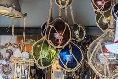 Colores, reflejos y transparencias (ninestad) Tags: tienda objetos souvenirs mar pesca conchas cuerdas nudos bolas colores caracola