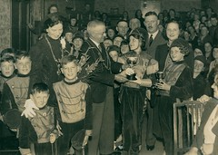 Presenting a trophy to the George Street Jazz Band (Tyne & Wear Archives & Museums) Tags: johngrantham lordmayor newcastleupontyne 1930s northeastengland tyneside jazzband georgestreet celebration prize trophy presentation socialhistory blackandwhitephotograph servingthecity archives duty service interesting unusual fascinating georgestreetjazzband event unitedkingdom interior room wallpaper wall pattern paper costume uniform children adults smile crowd gathering trousers crease fabric tie shirt glasses shine chair rest timber standing seated necklace hat moustache distracted attentive
