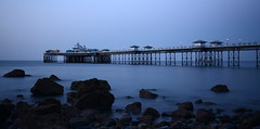 Eerie Blue. (Peter.S.Roberts) Tags: lighting longexposure blue sea cold beach strange night pier interestingness still interesting scary rocks sinister victorian calm structure creepy spooky wierd mysterious boardwalk serene bluehour unreal ghostly llandudno spectral frightening unnatural northwales unearthly eerieblue