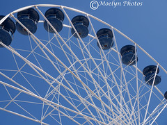 Blue and White-Close-up of a Ferris Wheel (moelynphotos) Tags: ferriswheel amusementpark closeup partialview metalspokes passengercars clearsky nopeople seasonal lookingup rides oceancity maryland horizontal landscapeformat outdoorfun moelynphotos