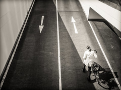 arrows (grizzleur) Tags: street woman bike bicycle lady streetphotography lane arrows biker arrow graphical lanes pushing olympusomdem5
