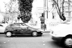 Always rushing (lorenzoviolone) Tags: longexposure england blackandwhite bw london cars monochrome trafficlight blackwhite traffic unitedkingdom streetphotography vehicles finepix fujifilm streetphoto crosswalk agfascala200 mirrorless vsco streetphotobw vscofilm fujix100s x100s fujifilmx100s travel:uk=londonapr16