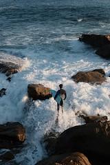 Surfer on the rocks (Carsten Waahlin) Tags: sunset rocks surfer bigwaves
