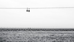 Three Doubles - Lissabon, Portugal (Sebastian Bayer) Tags: sea vacation two sky people blackandwhite bw holiday cars portugal water car bride meer wasser waves leute outdoor urlaub bridges himmel olympus structure menschen symmetric sw lissabon brcke zwei ropeway omd wellen gondel seilbahn brcken symmetrie gondeln schwarzweis drausen 124028 omdem5ii