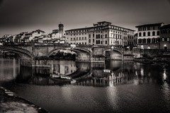 Reflecting on the Arno (Anthony Plancherel) Tags: architecture citiestowns external florence italy night nightscenes places time travel travelphotography architecturephotography bridge arch structure buildingstructure span buildings oldbuildings renaissance firenze italian italia canon1585mm canon70d canon monochrome blackandwhite bw whiteandblack sky cityscape river arnoriver riverarno europe european tuscany stone stonebridge reflections reflectedlight lights lamps streetlamps lightatnight dusk gloaming evening water reflectyourworld