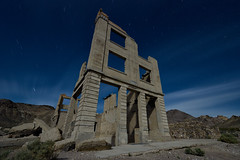 cook bank building. rhyolite, nv. 2016. (eyetwist) Tags: longexposure windows shadow sky building cars abandoned architecture night dark dead photography gold star nikon ruins long exposure shadows desert decay empty nevada ruin cook trails bank wideangle landmark mining fullmoon nv dirt american highdesert americana deathvalley lonely nikkor rhyolite desolate derelict nocturne beatty goldrush startrails typology mojavedesert wasteland eyetwist npy cookbankbuilding 1024mm d7000 capturenx2 eyetwistkevinballuff nikond7000 1024mmf3545g americantypology