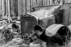 Rusting Away (Scosanf) Tags: blackandwhite bw monochrome colorado historical ford cars automobile rusty old classic outdoor weeds museum montrose wood weathered headlights aged vintage decay travel trip vacation summer canon eos ef2470mmf28lusm topazlabs