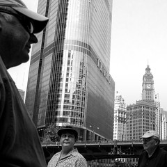 Walk With Giants (Andy Marfia) Tags: street bw chicago river iso200 loop candid 20mm trumptower wrigleybuilding chicagoriver f56 squarecrop riverwalk fromthehip 11250sec panasonicgm1