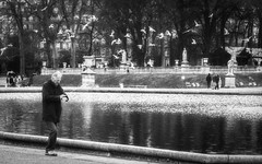 """Tlcommande (or, """"what time is it?"""") (Gabriel M.A.) Tags: leica bw man paris france fountain birds 50mm grain olympus summicron cropped f2 fontaine f28 omd tabbed jardinduluxembourg em5 16x10 leicasummicron50mmf20iv"""