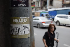 Hello My Name Is... (jcbkk1956) Tags: thonglo street bangkok thailand nikon nikkor 1855mmf3556 sticker lampost girl focus bokeh dof streetfurniture traffic umbrella candid
