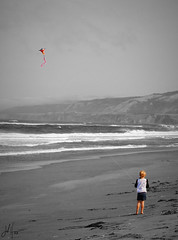 A girl and her kite (The Moon & Back) Tags: bw blackandwhite dark light shadow grey beach ocean waves coast sand kite fly sky selective color girl kids children landscape sea serene calm wind tide windy breeze