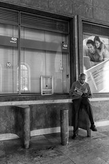 'Don't Look Back' (Canadapt) Tags: man reading poster overlook trainstation window kiosk seated juxtaposition lisbon portugal canadapt street bw