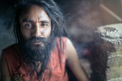 "Baba, the sadhu of a Kathmandus slum posing while smoking ganja. His temple collapsed after the earthquake. But Baba never feels sad. ""This is the power of Gods"" he said (Fabien Lasserre -) Tags: nepal eye look yoga canon beard intense bokeh smoke naturallight smoking kathmandu slum sadhu f12 ganja markiii eathquake bidonville bagmati tremblementdeterre  katamandou sdhu"
