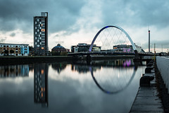 The Clyde Arc (Daveography.ca) Tags: clydearc arch waterfront sunset cloudy water reflections city gb uk archbridge clouds greatbritain unitedkingdom glasgow reflection scotland dusk river cloud archspan birdge rainy arc riverclyde skyline theclydearc clyderiver