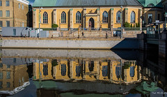 2016 - Baltic Cruise - Gothenburg Sweden - German Church Reflection (Ted's photos - For Me & You) Tags: 2016 balticcruise cropped gothenburg tedmcgrath tedsphotos vignetting christianchurch christinaechurchgothenburg germanchurch germanchurchgothenburg sweden gothenburgsweden tower churchtower reflection waterreflection people peopleandpaths streetscene street streetlamp railing railings cross shadow bollards
