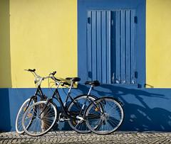 Aveiro bikes (Carolbreeze99) Tags: portugal bicycle shadow sun shade yellow blue vivid colour travel aveiro cliche transport wheels window sunlight matchpointwinner mpt505