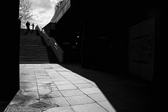 Under The Bridge (Places, Faces) Tags: street city bridge light england people urban blackandwhite bw sunlight london monochrome lines architecture composition mono shadows britain centre central steps perspective streetphotography silhouettes angles streetscene scene waterloo streetphoto capture passage lowkey brutalist peoplewatching robmchale