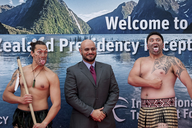 An attendee poses with New Zealand Maori performers