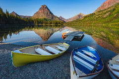 Primary Canoes (jeanineleech) Tags: morning blue red summer usa mountains reflection water yellow montana rocks colorful mt canoe shore canoes glaciernationalpark mountainpeak sinopahmountain