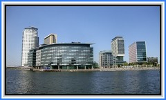Salford Quays 8. The Media Centre (Margaret Edge the bee girl) Tags: blue windows summer sun water architecture modern manchester outdoors grey still salfordquays bbc mediacentre