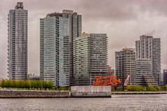 Under The Weather (nywheels) Tags: newyorkcity trees sky water rain clouds buildings cloudy towers historic eastside bigapple rooseveltisland pepsisign iconpepsisign
