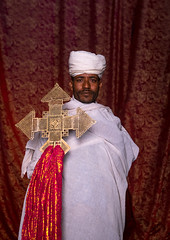 Portrait of an ethiopian orthodox priest holding a cross inside a rock church, Amhara region, Lalibela, Ethiopia (Eric Lafforgue) Tags: africa travel red portrait man color men vertical outdoors worship cross adult african curtain faith religion unescoworldheritagesite celebration holy indoors sacred priest christianity shawl spirituality ethiopia orthodox religiouscelebration oneperson traditionalculture lalibela hornofafrica ethiopian eastafrica thiopien etiopia abyssinia ethiopie traditionalclothing etiopa lookingatcamera onlymen onemanonly waistup onematuremanonly  etiopija 1people ethiopi  africanculture etiopien etipia  etiyopya  amhararegion         semienwollozone ethio163659