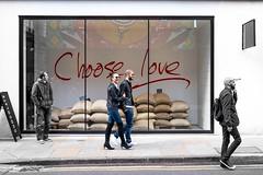 Choose Love (Silver Machine) Tags: street men london window sunglasses walking lumix couple candid streetphotography shoreditch windowdisplay sandbags lumixg lumixg20mmf17 lumixg5 fujiholicsphotowalklondonmay2016