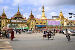 The golden Botahtuang Pagoda towering above the streets of Yangon (Bn) Tags: road street old city people car sunshine umbrella hair temple gold cycling pagoda high topf50 gate locals traffic buddha candid yangon burma stupa buddhist taxi colonial bikes monk capitol infrastructure million myanmar years former six buddism birma destroyed religions hollow seaport rebuild 2500 slums rangoon pilgrims dazzling overwhelmed entree botahtaung 40m gautama 50faves botataung kyats fietstaxi botatuang 1000militaryofficers