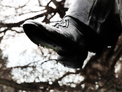 Wet Shoes (Steve Taylor (Photography)) Tags: newzealand christchurch sculpture brown white black tree art silhouette statue metal shoe spring branch bokeh canterbury drip nz trousers southisland laces hagleypark