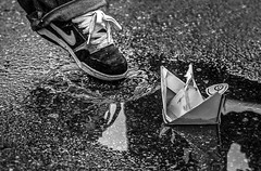 Paper boat. When all is possible... (N Medd) Tags: boy blackandwhite bw white black reflection fall rain childhood paper children puddle foot boat spring shoes child play running splash paperboat