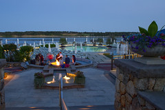 Before the Summer Crowds (brucetopher) Tags: lighting longexposure friends light party vacation people holiday men water pool umbrella relax fire evening twilight women friend couple exposure darkness stonework group patio deck ambience firepit happypeople beachumbrella vacationers hardscape partiers peoplebythefire