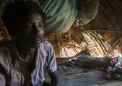 Afar tribe man inside his hut, Afar region, Afambo, Ethiopia (Eric Lafforgue) Tags: poverty africa portrait people house color home horizontal outdoors photography bed day village african muslim poor lifestyle property tribal indoors hut simplicity nomad ethiopia tribe oneperson developingcountry lookingaway hornofafrica ethiopian afar nomadic eastafrica burra abyssinia tribesman greatriftvalley ruralscene onemanonly waistup nonurbanscene danakil 1people indigenousculture africanculture afarregion africantribe nomadicpeople afambo ethio162625