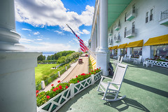_DSC3249 Grand Hotel Front Porch (Charles Bonham) Tags: architecture landscape outdoor lawn flags rockingchair geraniums pillars lilacfestival frontporch mackinacisland lakehuron mackinacbridge straitsofmackinac thegrandhotel michiganupperpeninsula cumulusclouds summerhotel sonya7r charlesbonhamphotography sonyzeissfe1635mmf4